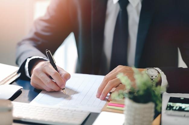 Scrittura della mano dell'uomo d'affari sul lavoro di ufficio mentre sedendosi alla scrivania in ufficio moderno.