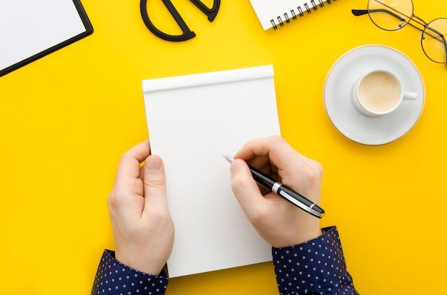 Scrittura della mano di vista superiore sul taccuino