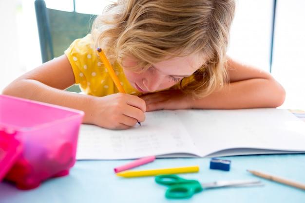 Scrittura della ragazza del bambino dello studente del bambino con i compiti sullo scrittorio