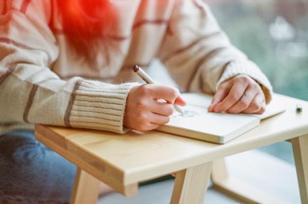 Scrittura della ragazza in un taccuino