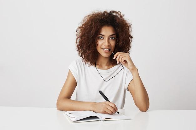 Scrittura di pensiero della ragazza africana in taccuino che sorride sopra la parete bianca. copia spazio.