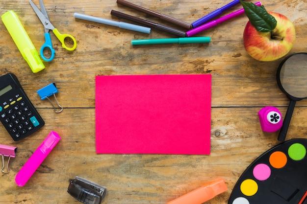 Scrittura di strumenti e mela disposti in cerchio con la nota adesiva in mezzo