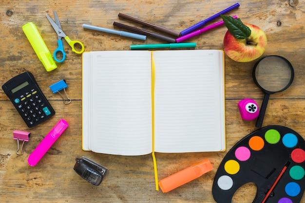 Scrittura di strumenti e mela messi in cerchio con il quaderno al centro