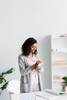 Scrittura etnica della giovane donna sui appunti in ufficio