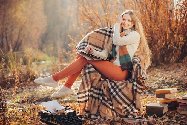 Scrittura felice della donna nel parco di autunno