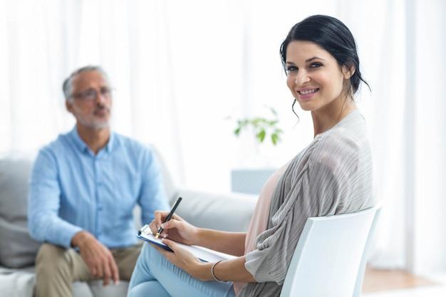 Scrittura femminile di medico sulla lavagna per appunti mentre consultando un uomo a casa