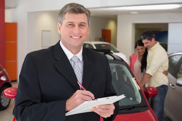 Scrittura sorridente dell'uomo d'affari sulla lavagna per appunti