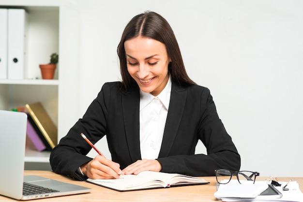 Scrittura sorridente della giovane donna sul diario con la matita su una scrivania