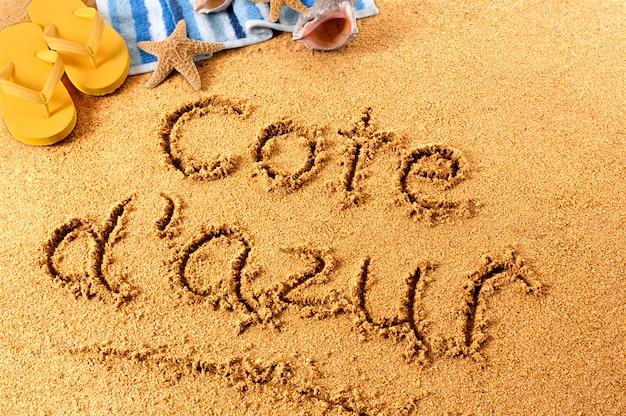 Scrittura sulla spiaggia della costa azzurra