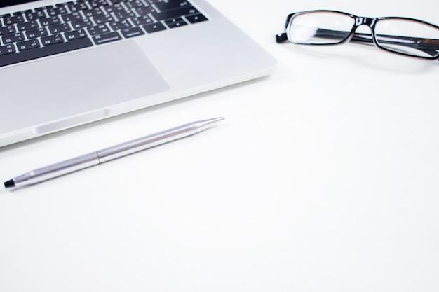 Scrivania bianca con computer e altri articoli per ufficio.