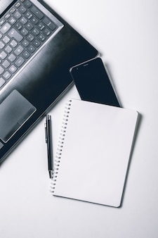 Scrivania bianca con il computer portatile, lo smart phone e la pagina in bianco del taccuino. vista dall'alto
