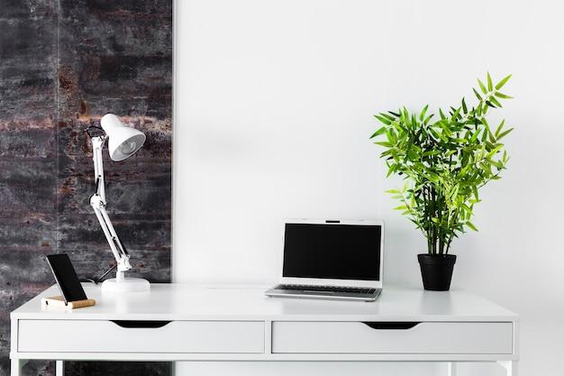 Scrivania bianca con laptop e lampada