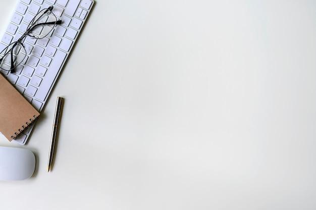 Scrivania bianca con sfondo bianco tastiera, mouse, penna, occhiali e notebook