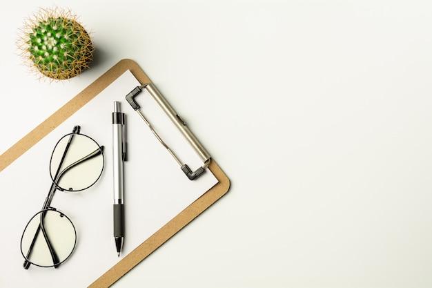 Scrivania bianca con una penna e occhiali.
