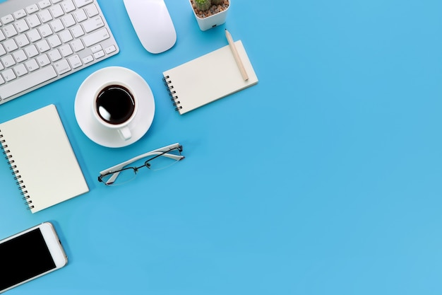 Scrivania blu pastello con computer e forniture per ufficio