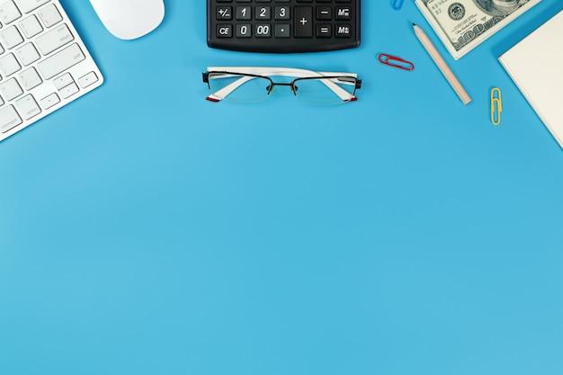 Scrivania con computer, occhiali, calcolatrice e matita su blu
