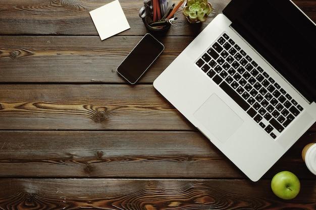 Scrivania con computer portatile, forniture e mela verde