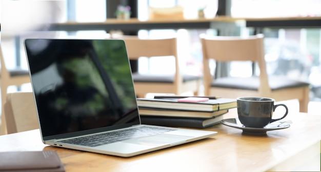 Scrivania con computer portatile, libri e sfondo di ufficio affari.