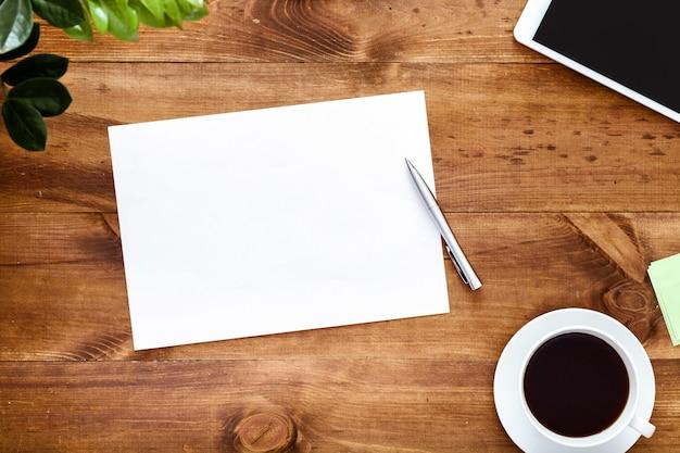 Scrivania con il taccuino in bianco aperto per le note sulla tavola di legno marrone