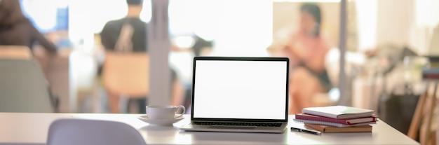 Scrivania con laptop schermo vuoto e notebook nella stanza di partizione di vetro