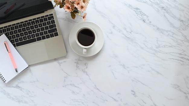 Scrivania con struttura in marmo e laptop, penna, taccuino, caffè con fiori sul tavolo spazio copia.