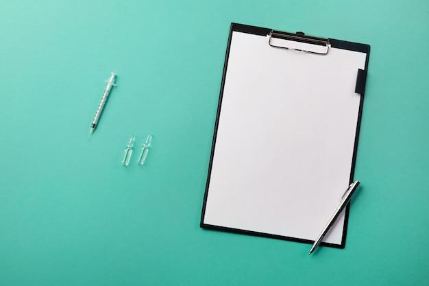 Scrivania con tablet, penna, siringa e fiale