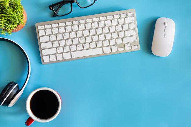Scrivania con tazza di caffè, tastiera, mouse ottico, occhiali, cuffie e cactus