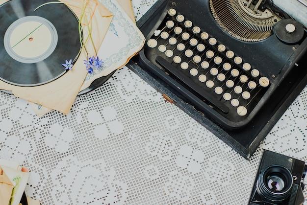 Scrivania d'epoca con macchina da scrivere, pila di vinile e fotocamera sulla tovaglia