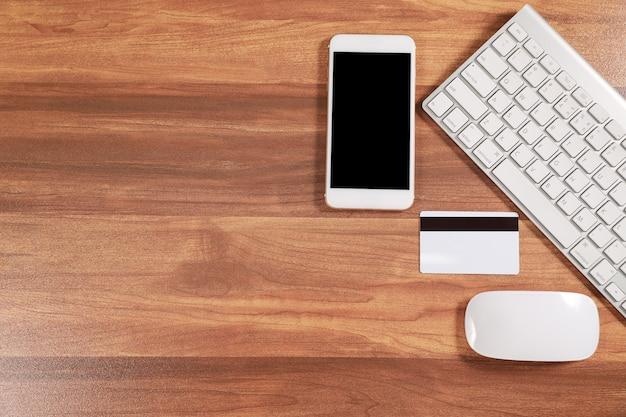 Scrivania da lavoro in legno con computer, smartphone e carta di credito