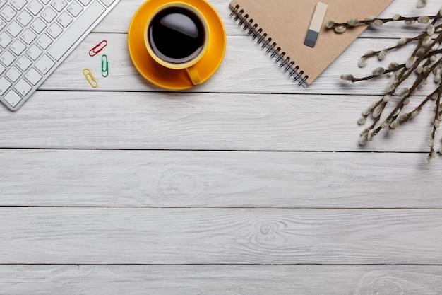 Scrivania da tavolo con piano e vista dall'alto. area di lavoro con taccuino vuoto, tastiera, amaretto, forniture per ufficio e tazza di caffè