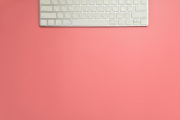Scrivania da tavolo con piano e vista dall'alto. area di lavoro con tastiera su sfondo rosa.