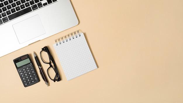 Scrivania da ufficio con calcolatrice e blocco note; penna contro sfondo beige