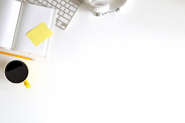 Scrivania da ufficio con computer, cuffie, caffè, taccuino e matita.