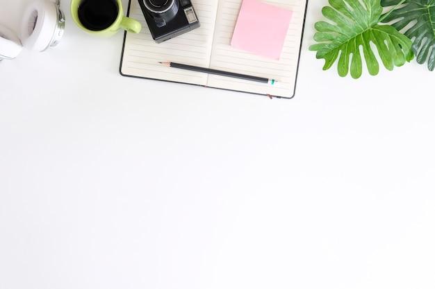 Scrivania da ufficio con macchina fotografica, matita, carta da lettere e cuffie con caffè sull'area di lavoro