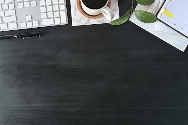 Scrivania da ufficio con vista dall'alto. area di lavoro con tastiera e articoli per ufficio sul tavolo di legno nero.