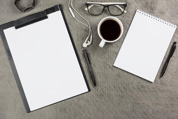 Scrivania da ufficio grigia con tazza di caffè; auricolari e occhiali