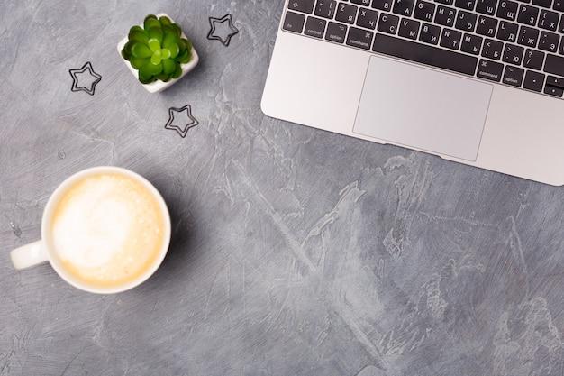 Scrivania da ufficio grigia piatta con computer portatile argento, tazza da caffè e cancelleria