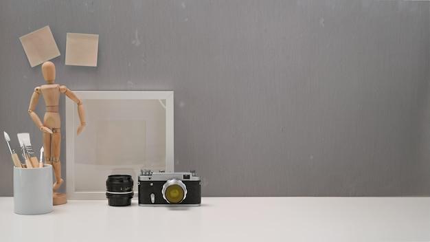 Scrivania da ufficio minimalista con macchina fotografica d'epoca, roba e copia spazio