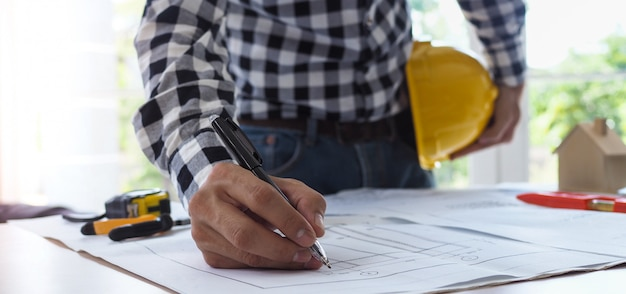 Scrivania dell'appaltatore del progetto che visualizza il piano della struttura dell'edificio