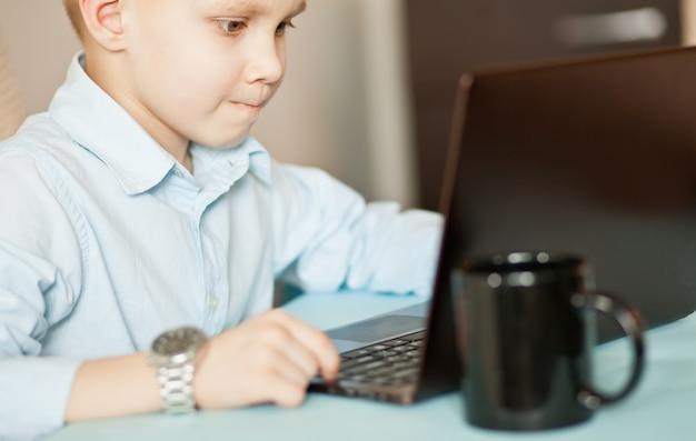 Scrivania dell'area di lavoro con computer portatile e tazza di caffè. piccolo ragazzo sveglio di affari che si siede alla tavola e che guarda sui documenti importanti. kid apprendimento online.