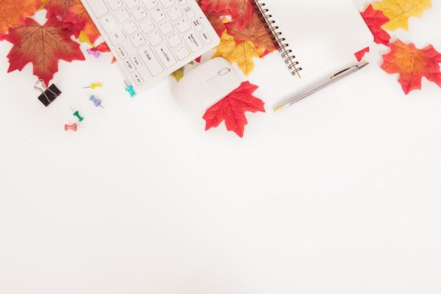 Scrivania di affari nel concetto di stagione di autunno con le foglie di acero variopinte e gli stazionari, su bianco