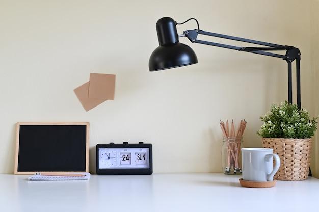 Scrivania di area di lavoro con forniture per ufficio sul tavolo.