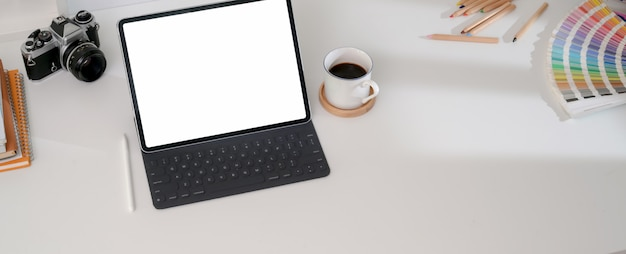 Scrivania di design con tablet, tazza di caffè, matite colorate, macchina fotografica e altri accessori