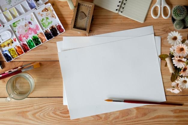 Scrivania di designer o artista con acquerello, pennello, matite e colori.