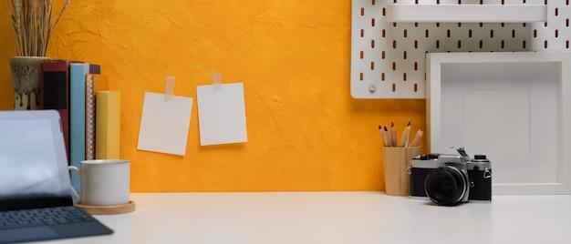 Scrivania domestica creativa con copia spazio, tavoletta digitale, macchina fotografica, articoli di cancelleria, libri e decorazioni