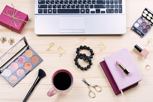 Scrivania femminile con articoli di cancelleria, laptop, accessori moda, fiori e prodotti per il trucco