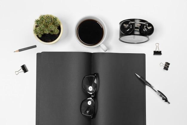 Scrivania in bianco con il taccuino e la tazza di caffè neri, vista superiore
