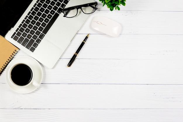 Scrivania in legno bianco con notebook vuoto e altri articoli per ufficio