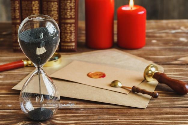 Scrivania in legno con clessidra vintage e vecchia lettera con sigillo a terra