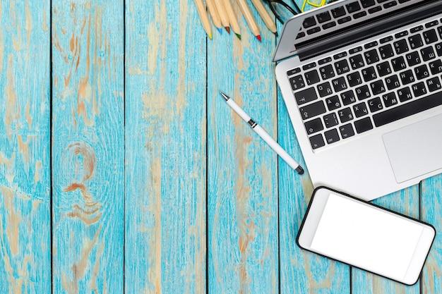 Scrivania in legno con laptop e articoli per ufficio. vista dall'alto sullo sfondo